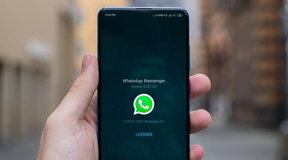 Смартфон в руке с логотипом WhatsApp на экране