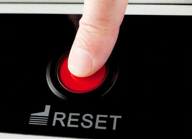 Палец на красной кнопке Reset