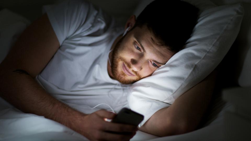 Молодой мужчина смотрит смартфон перед сном