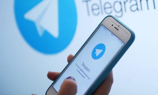 Смартфон с запущенным Телеграм в руках