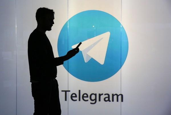 Темная фигура человека со смартфоном в руках на фоне логотипа Телеграм