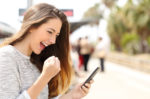 девушка со смартфоном радуется