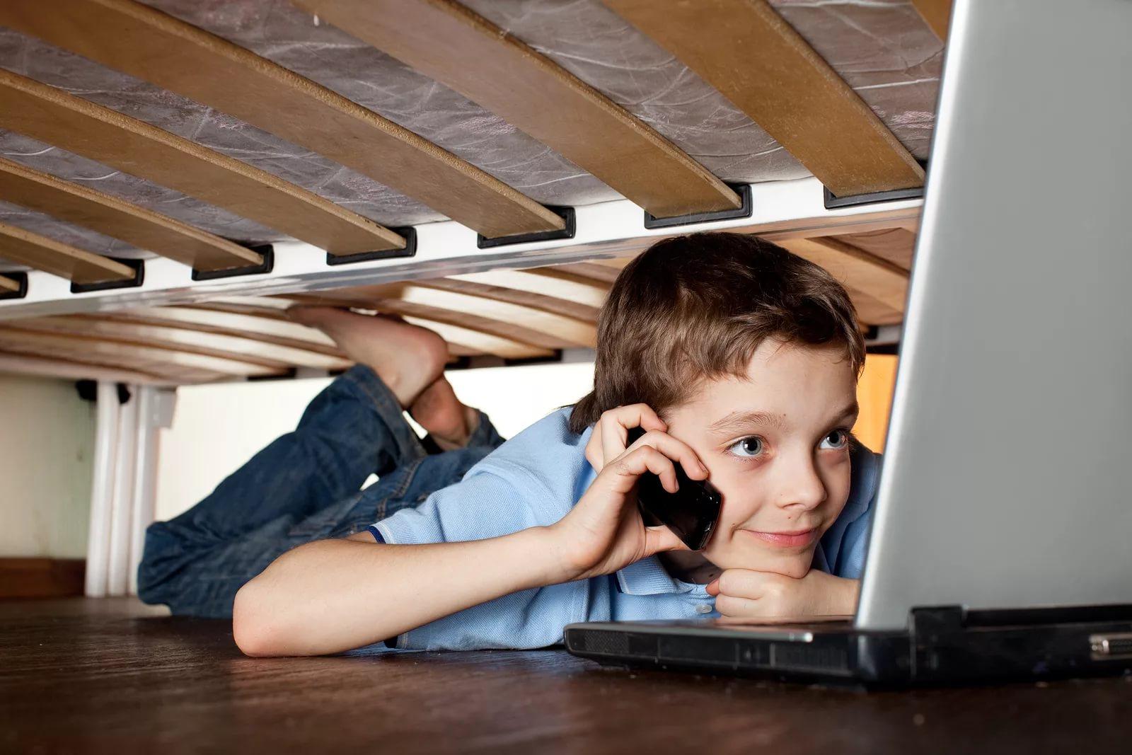 Ребенок под кроватью с ноутбуком