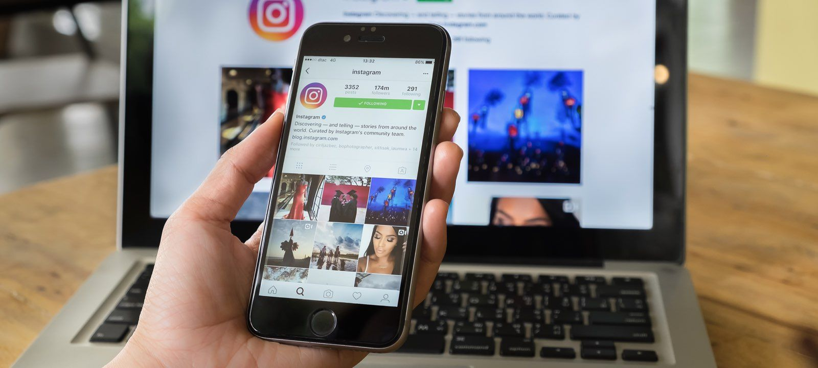 Смартфон с открытым Инстаграм в руке на фоне открытого ноутбука