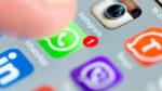 Палец на иконке Ватсап на экране смартфона